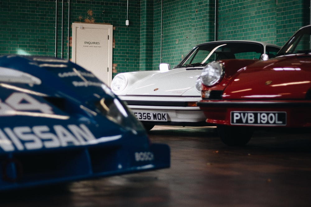 three white, red, and blue Porsche sports coupes inside room