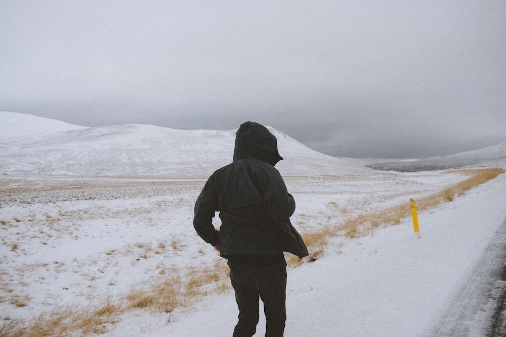 person wearing black jacket walking on snow field at daytime