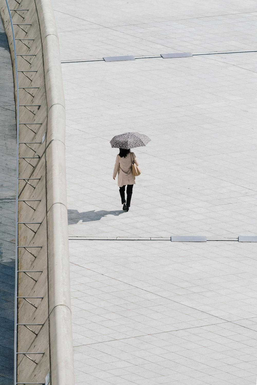 woman walking while wearing umbrella