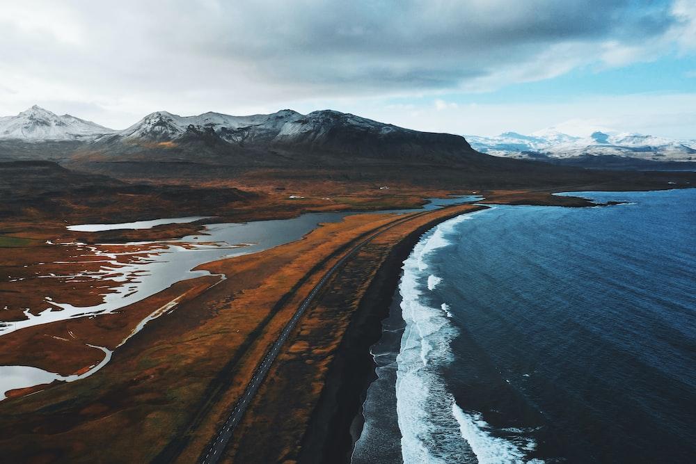 brown mountain near ocean