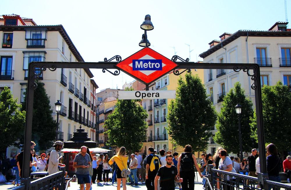 people standing under Metro Opera signage during daytime