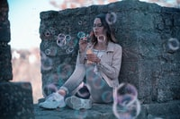 woman playing with bubbles while leaning on concrete wall