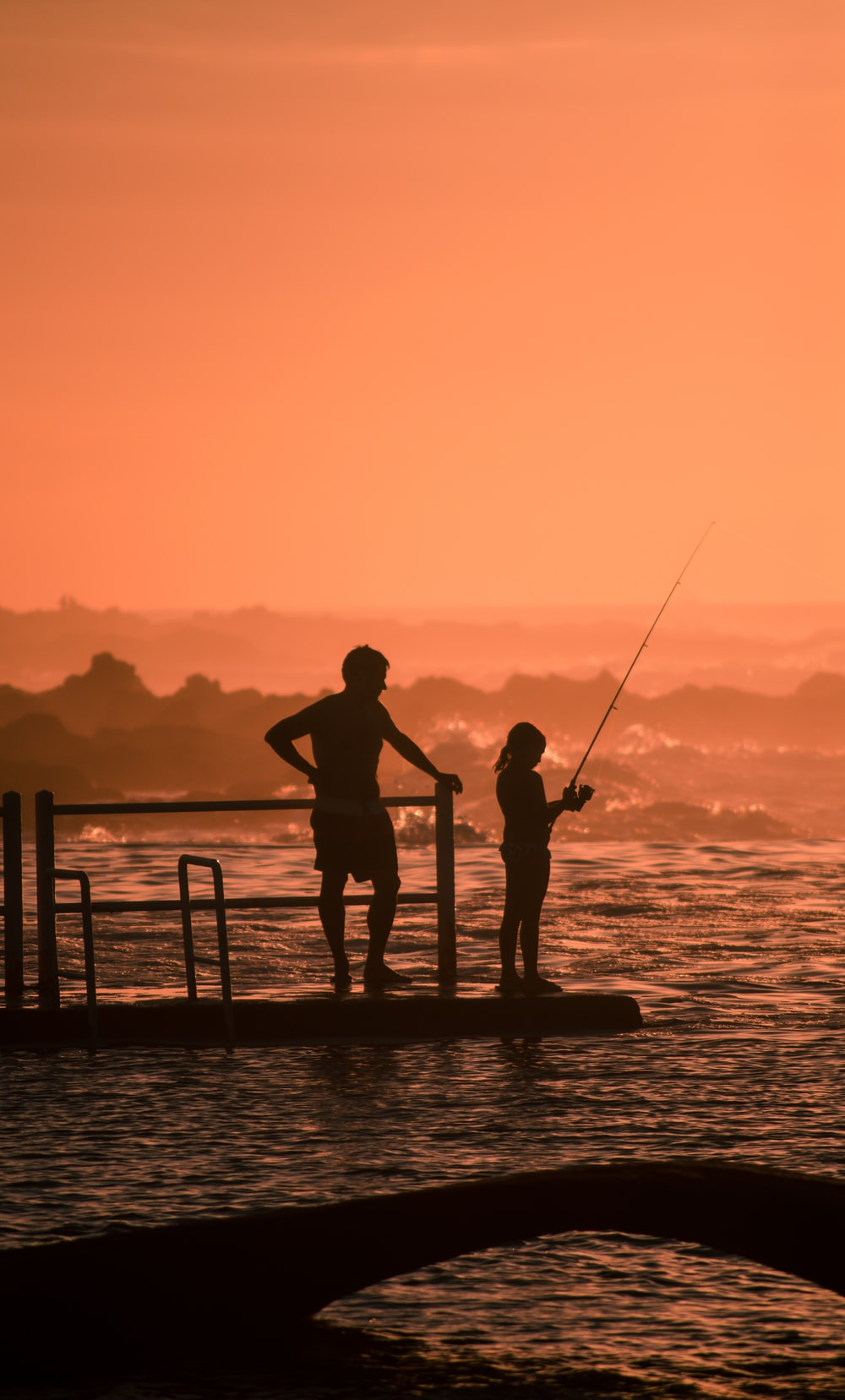 silhouette of man and girl fishing during sunset