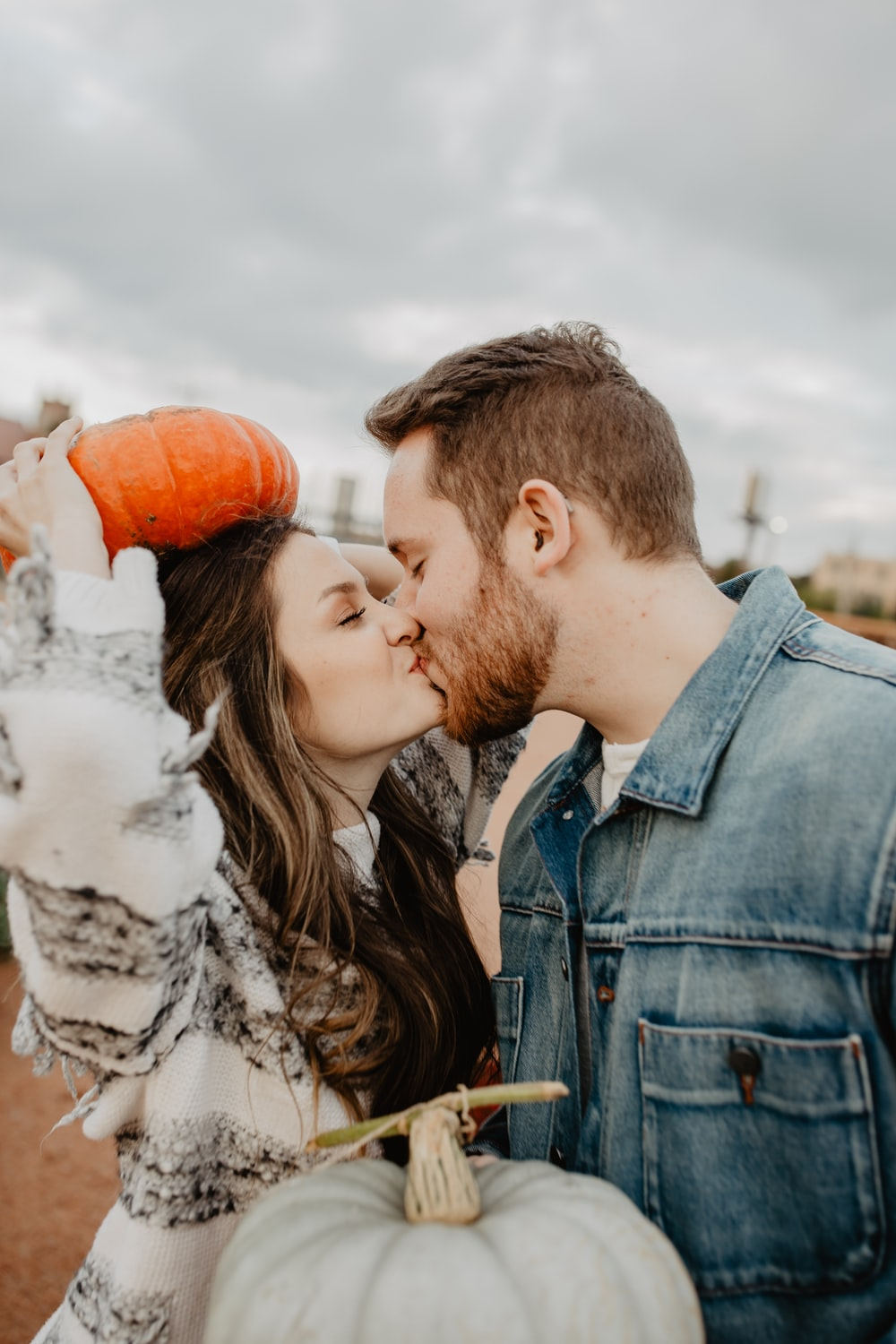 man and woman kissing holding squash during daytime