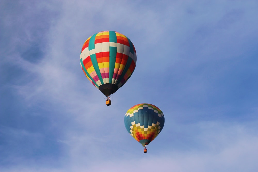 two multicolored hot air balloons floating on air