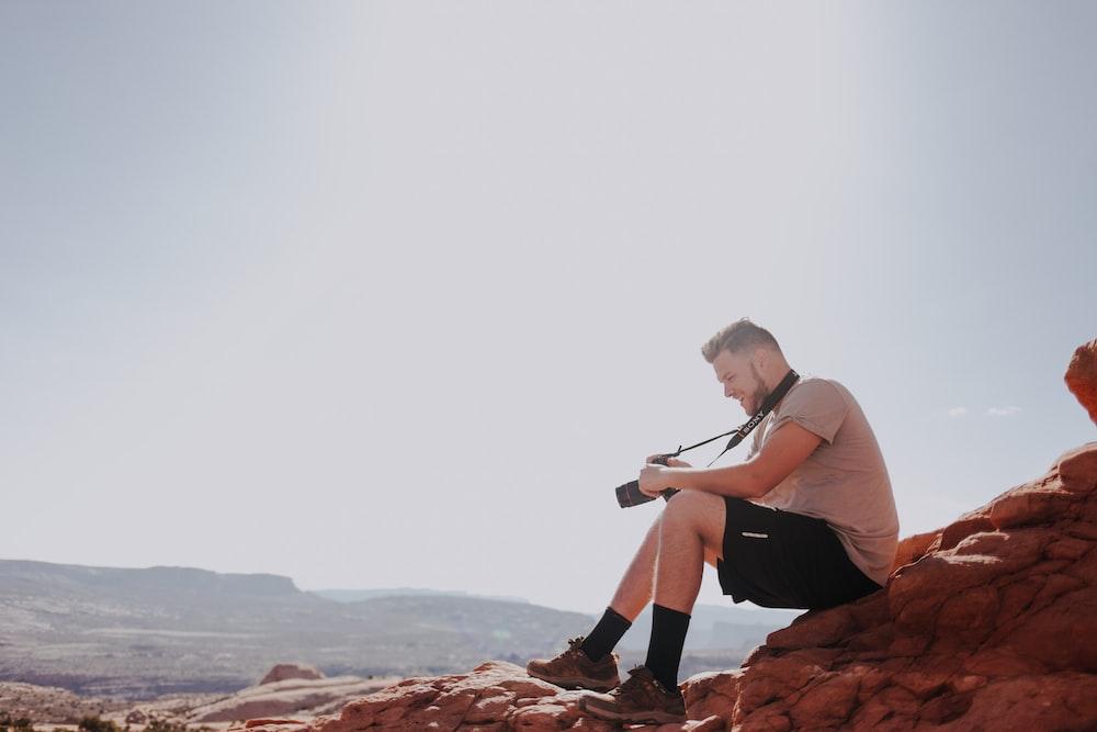man sitting on rock formation holding camera