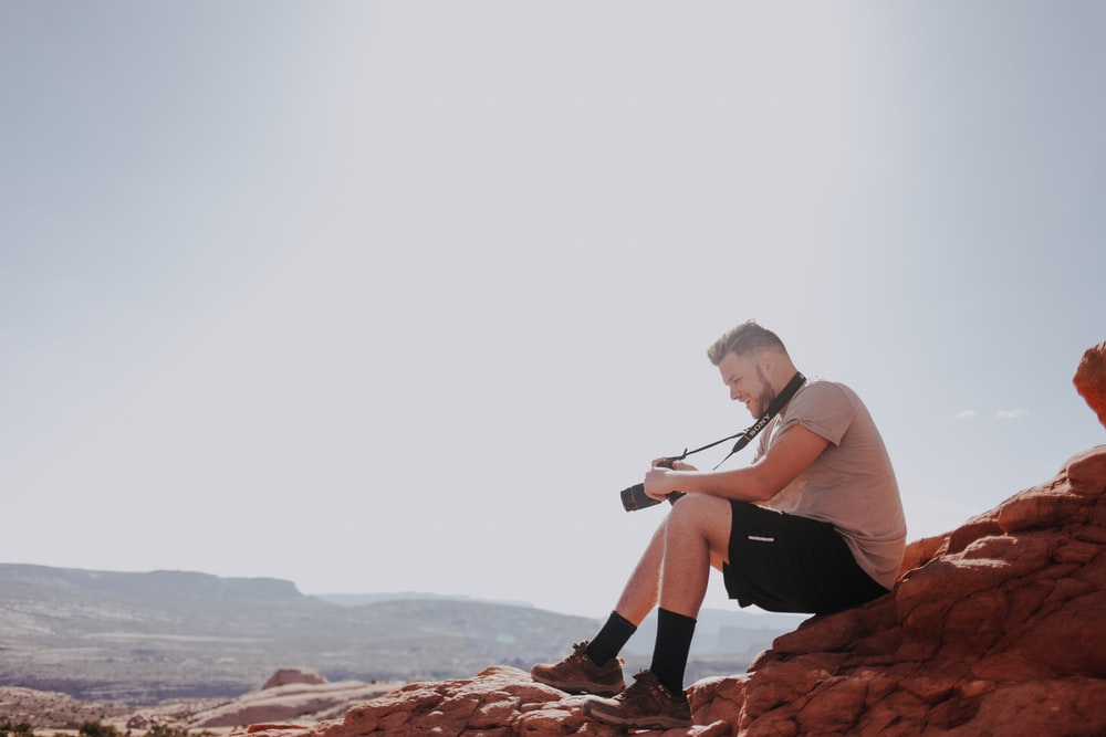 man sitting on rock formation holding camera