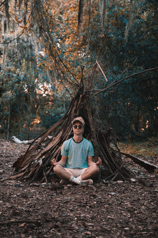 man meditating under trees