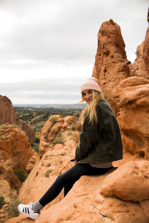 woman in black denim jacket sitting on rock formation during daytime