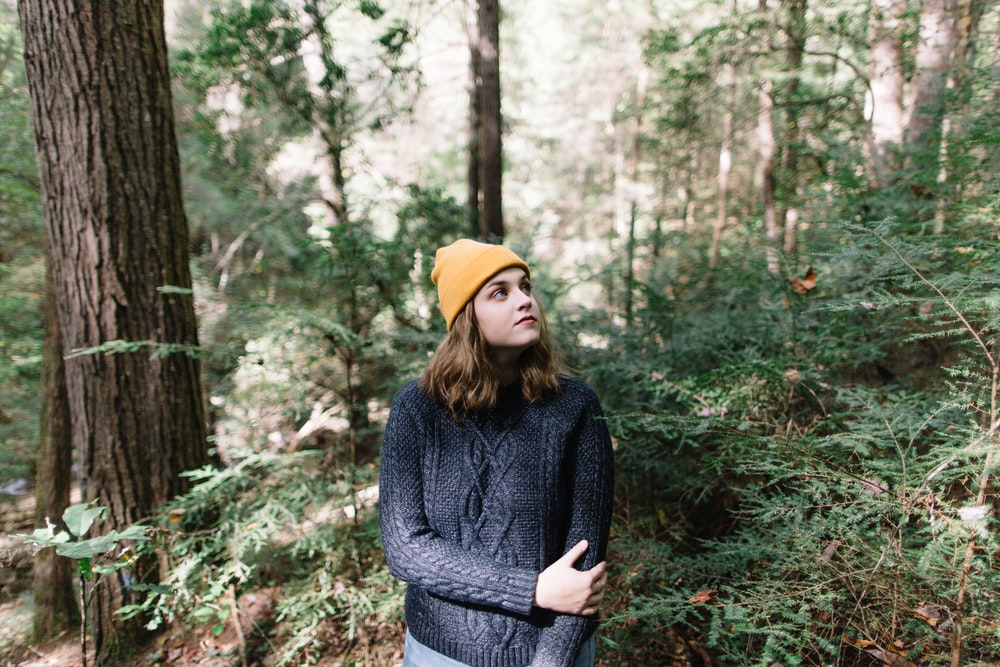 selective focus photography of woman standing in woods