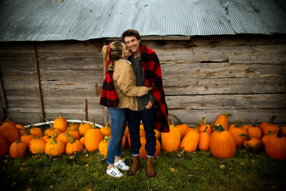 woman kissing man near pumpkins