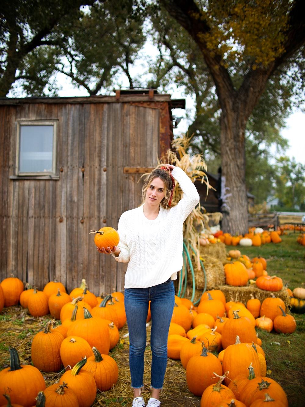 woman carrying orange pumpkin