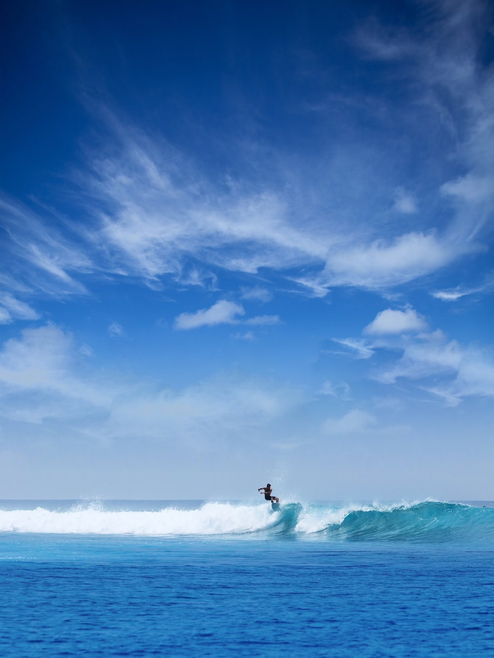 man surfing during daytime under white cloudy sky