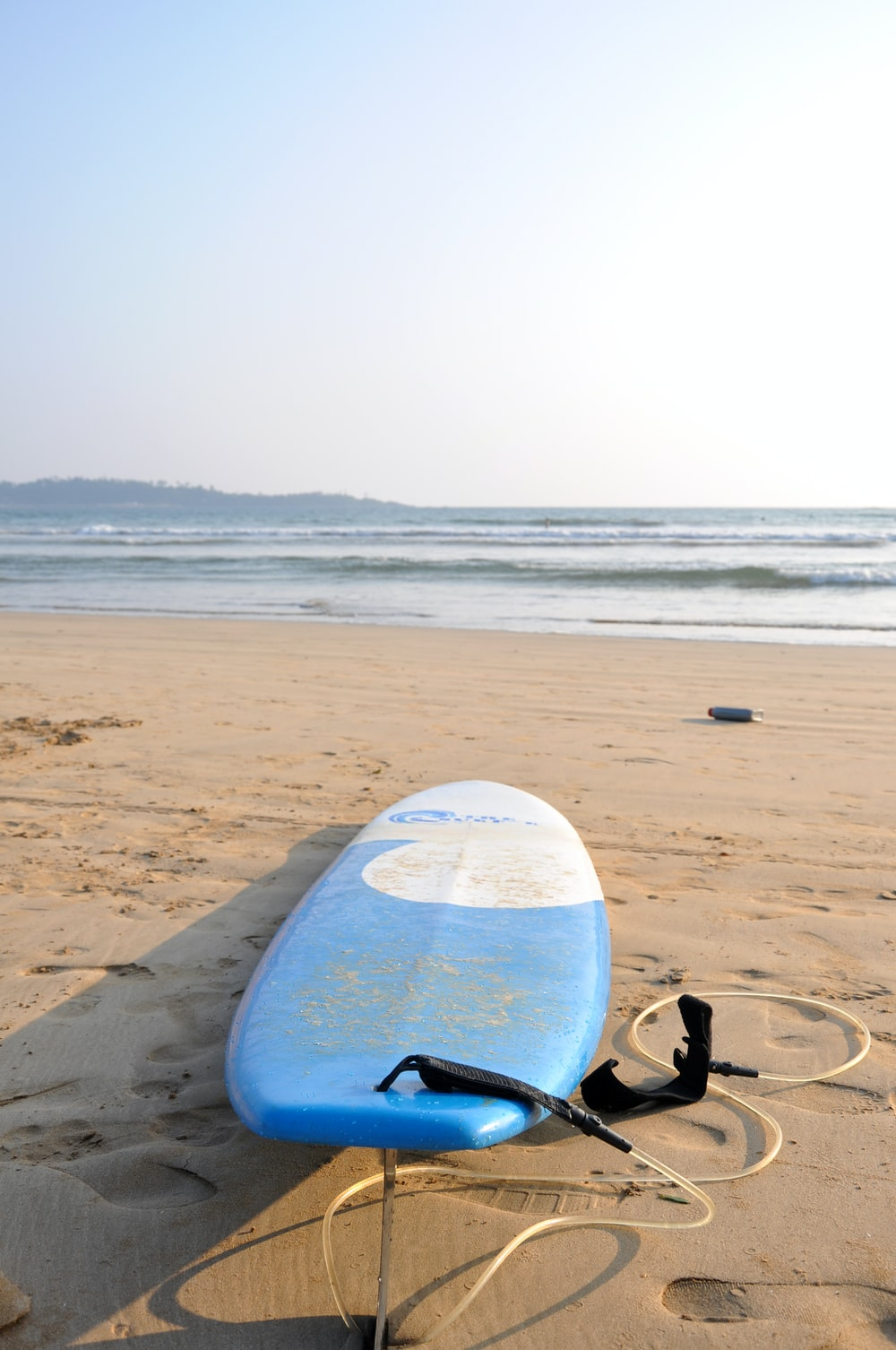 blue and white surfboard on seashore