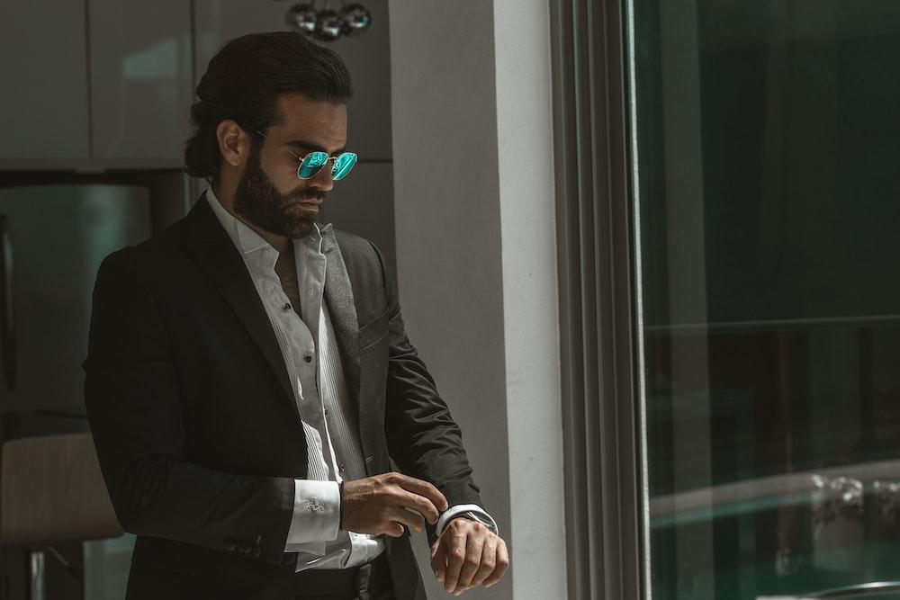 man wearing black coat over white dress shirt fixing his cuffs