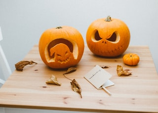 two orange pumpkins on brown wooden table