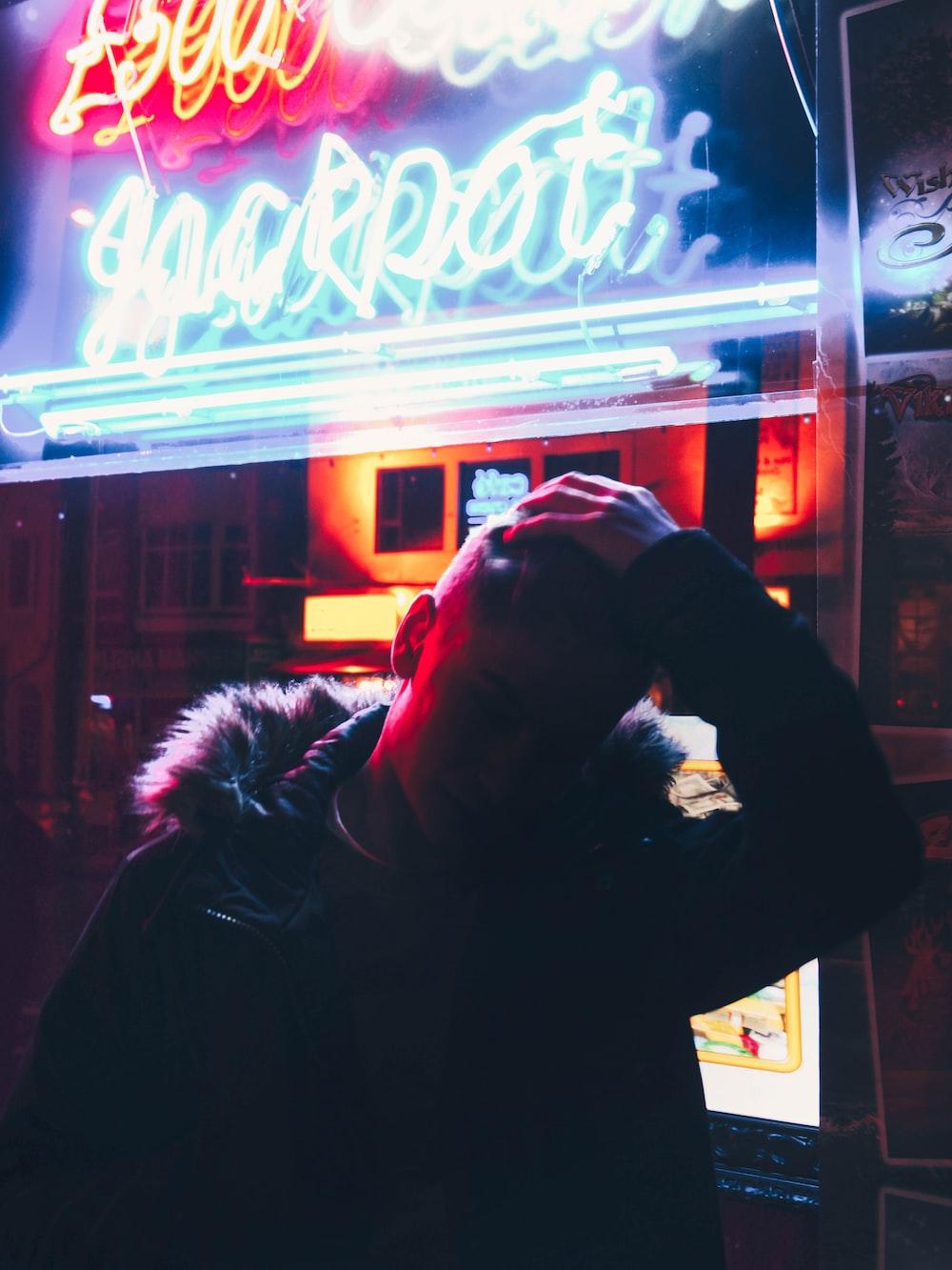 man standing near neon signs