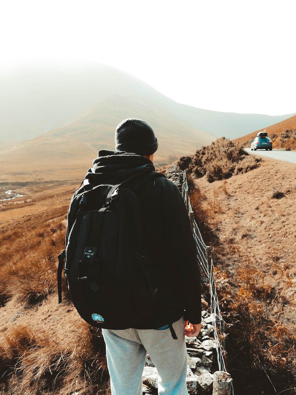 man in hoodie and backpack walking on stairs