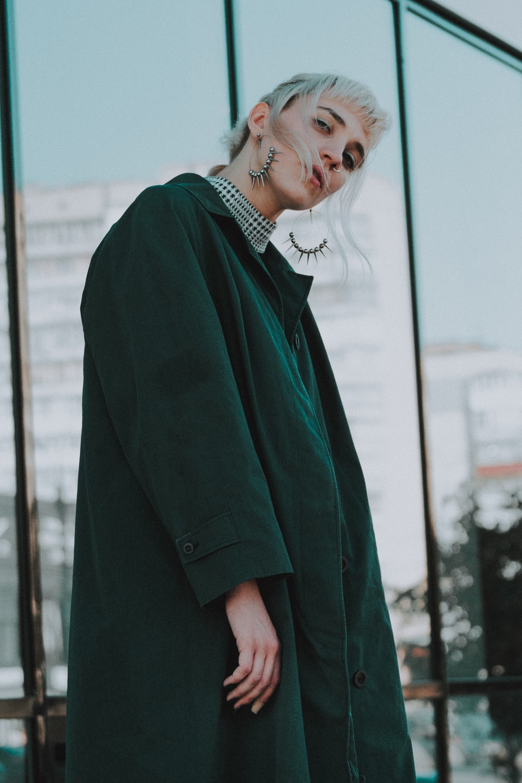 woman wearing black coat standing near clear glass wall