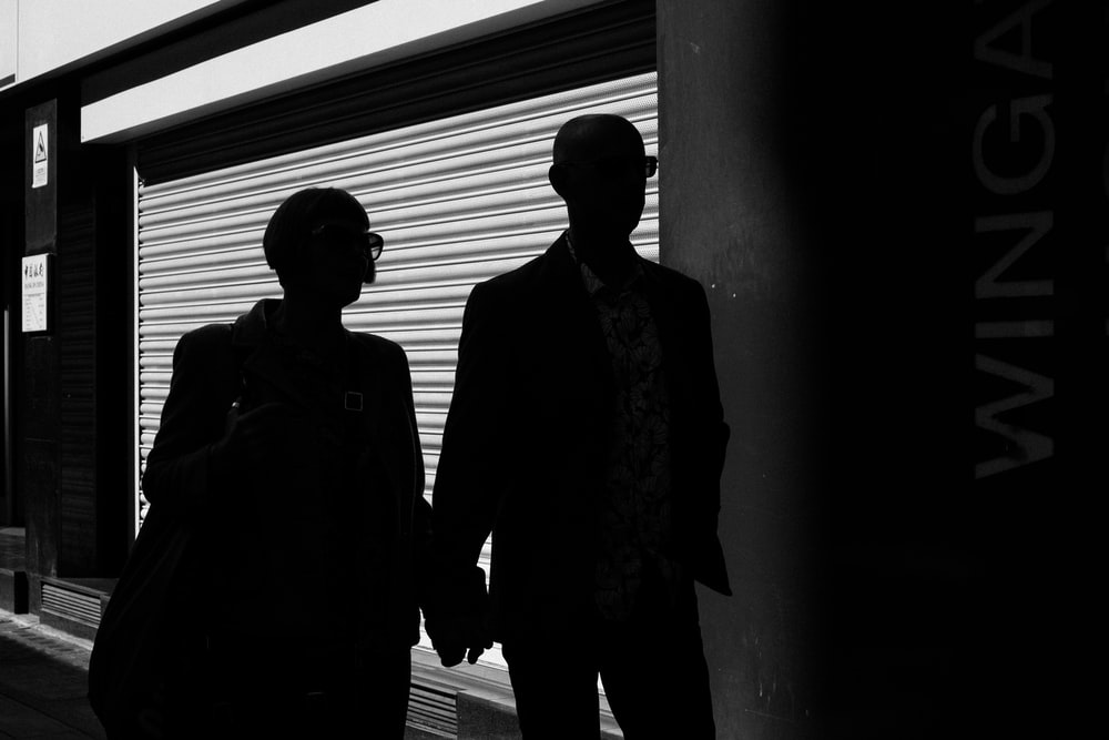 silhouette of man and woman walking inside building
