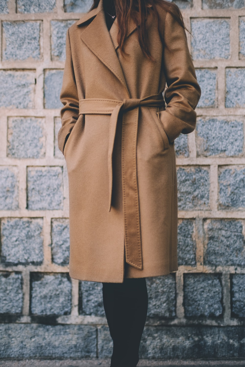 woman wearing brown single-breasted coat standing in front of gray brick wall