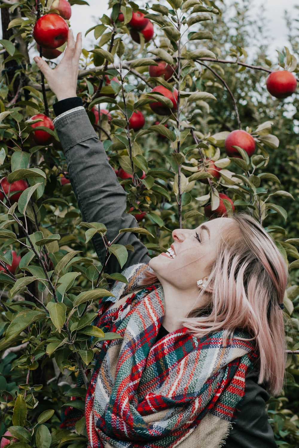 woman reaching for apple relating to the fact that apple cider vinegar can be useful in easing arthritis pain.