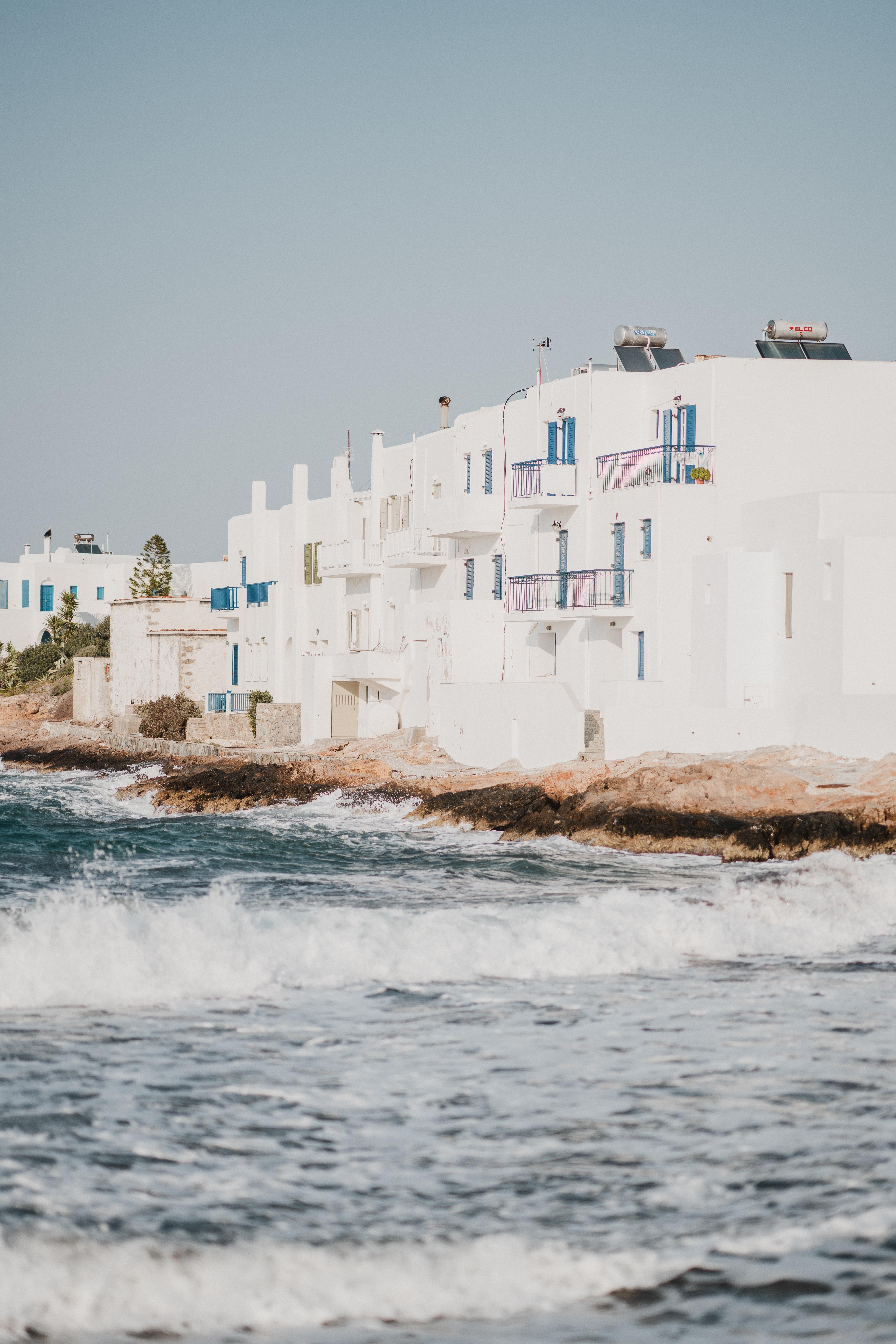 sea waves crashing on shore with house