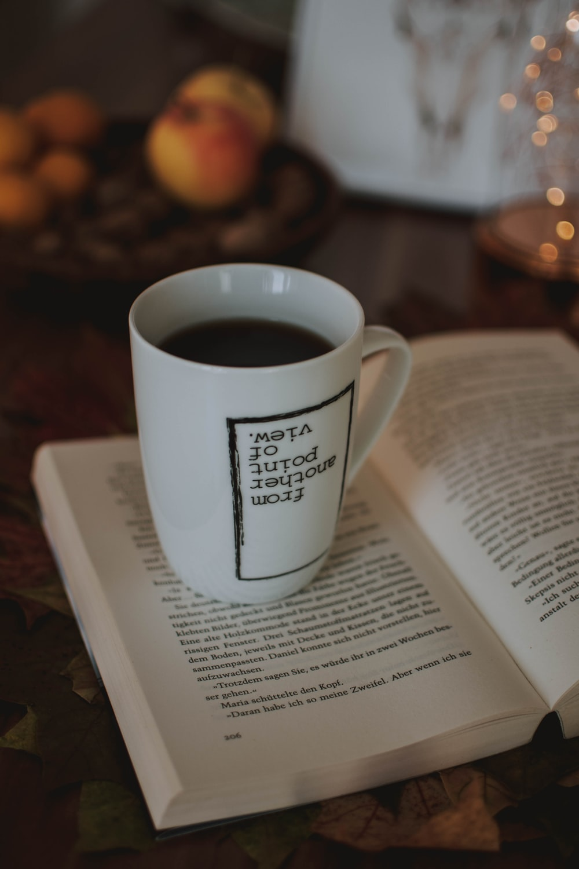 filled mug on opened book