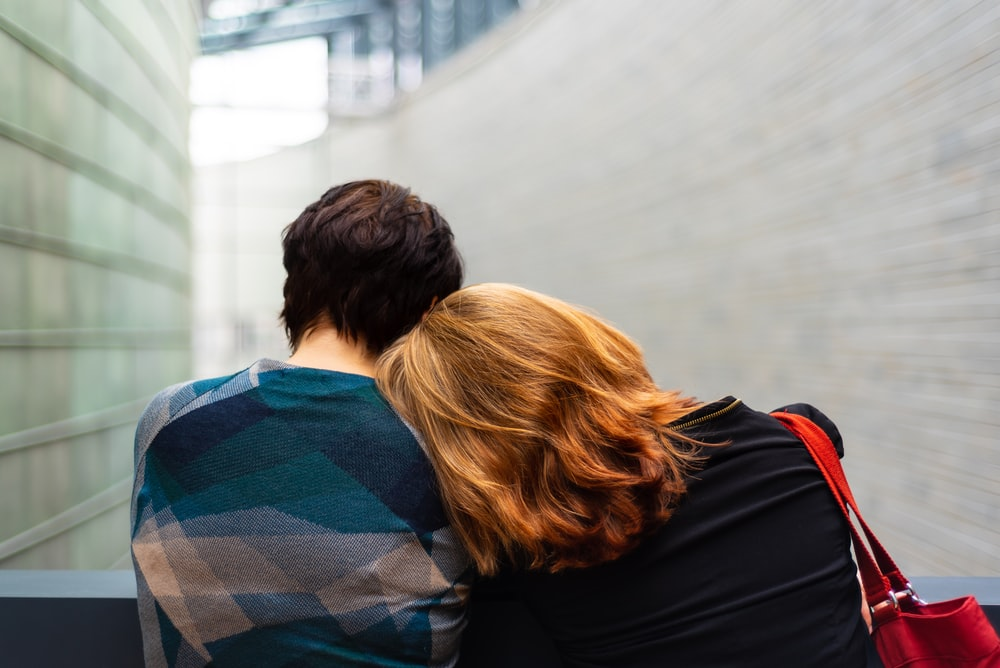 a woman rests her head on another person's shoulder
