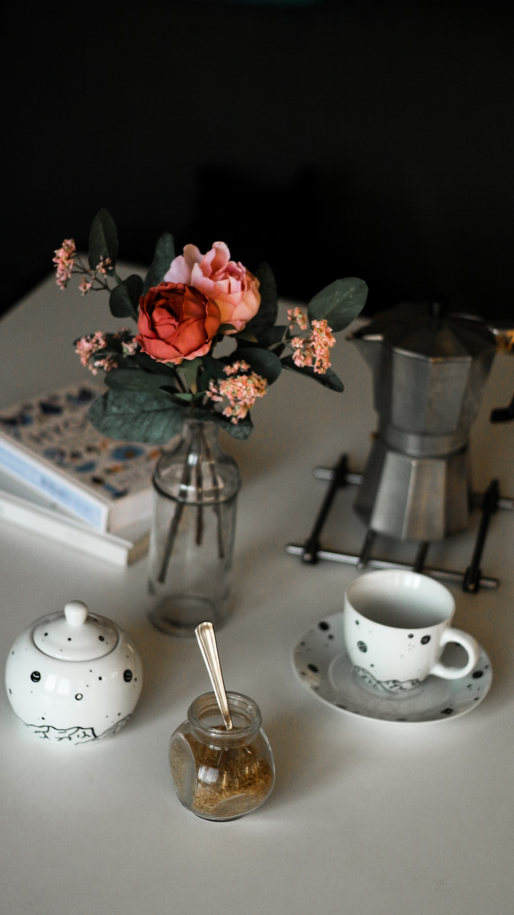 teacup by kettle and vase all on table top