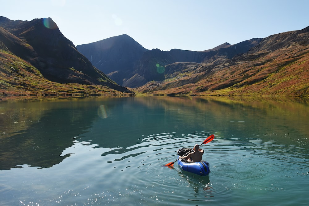 man riding on kayak surrounded by mountains