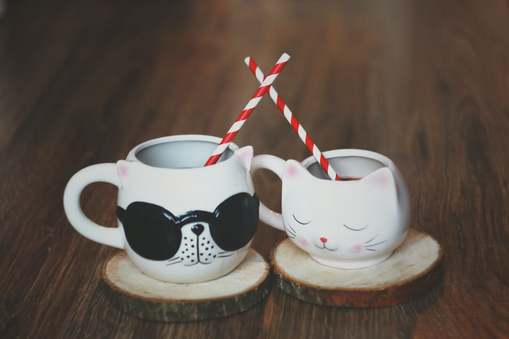 two ceramic cat shaped cups with wood slice coasters and with straws