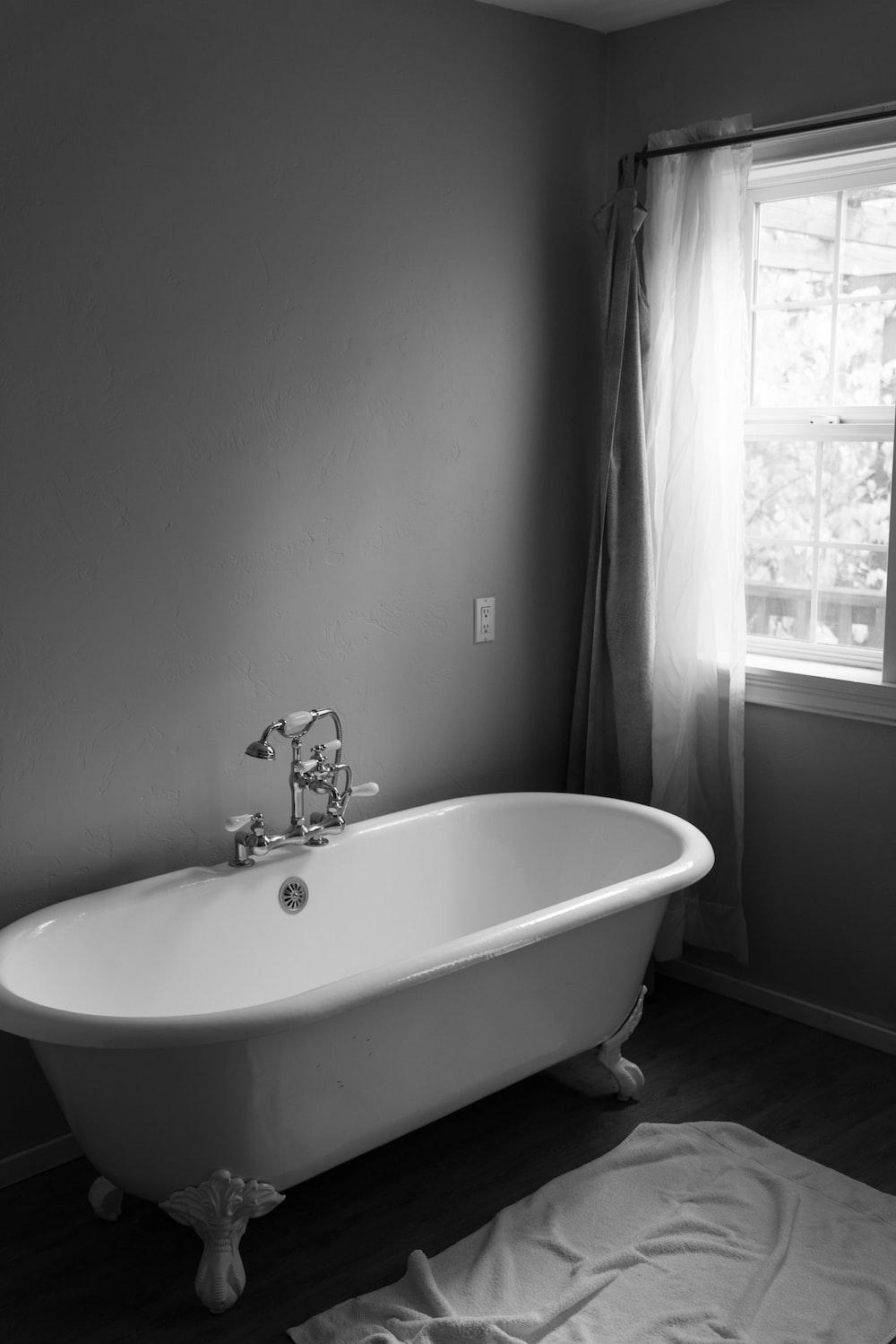 white ceramic bath tub inside room