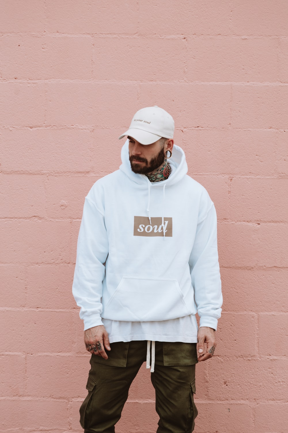 man wearing white pullover hoodie standing against the wall