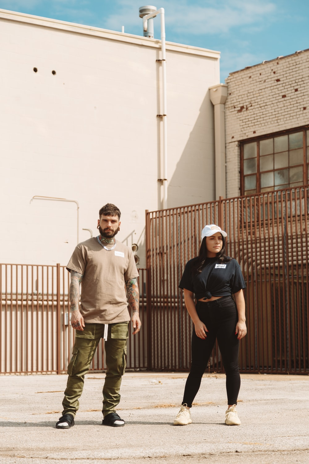 man and woman standing on front of brown building