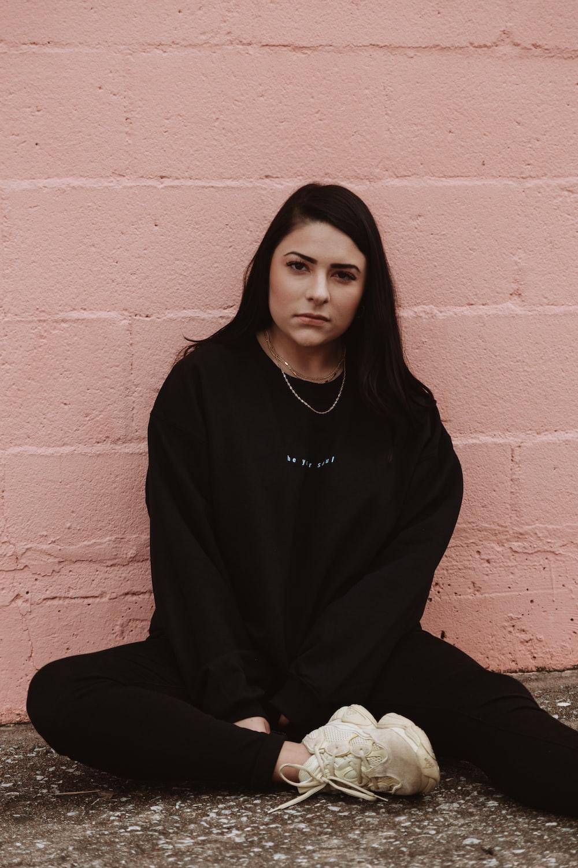 woman sitting near wall