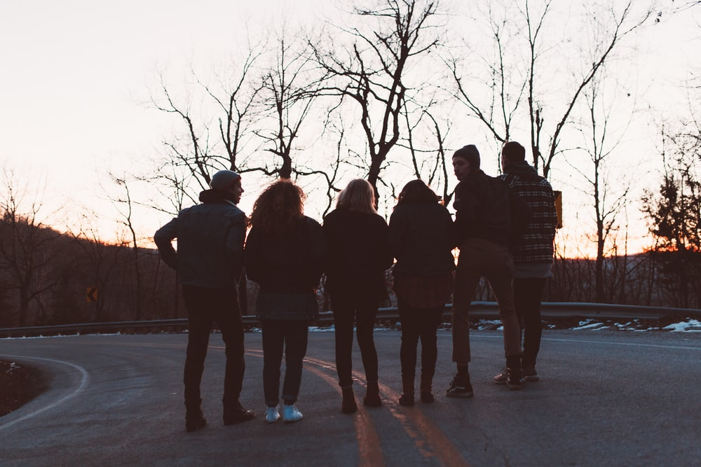 silhouette photography of six people standing on road