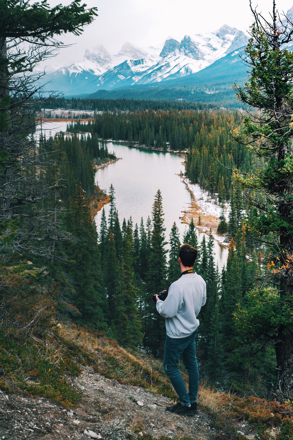 man wearing sweater standing on cliff watching river