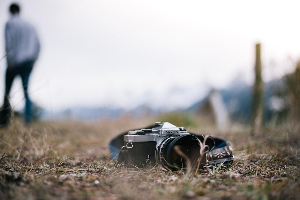 black and gray Nikon camera on ground