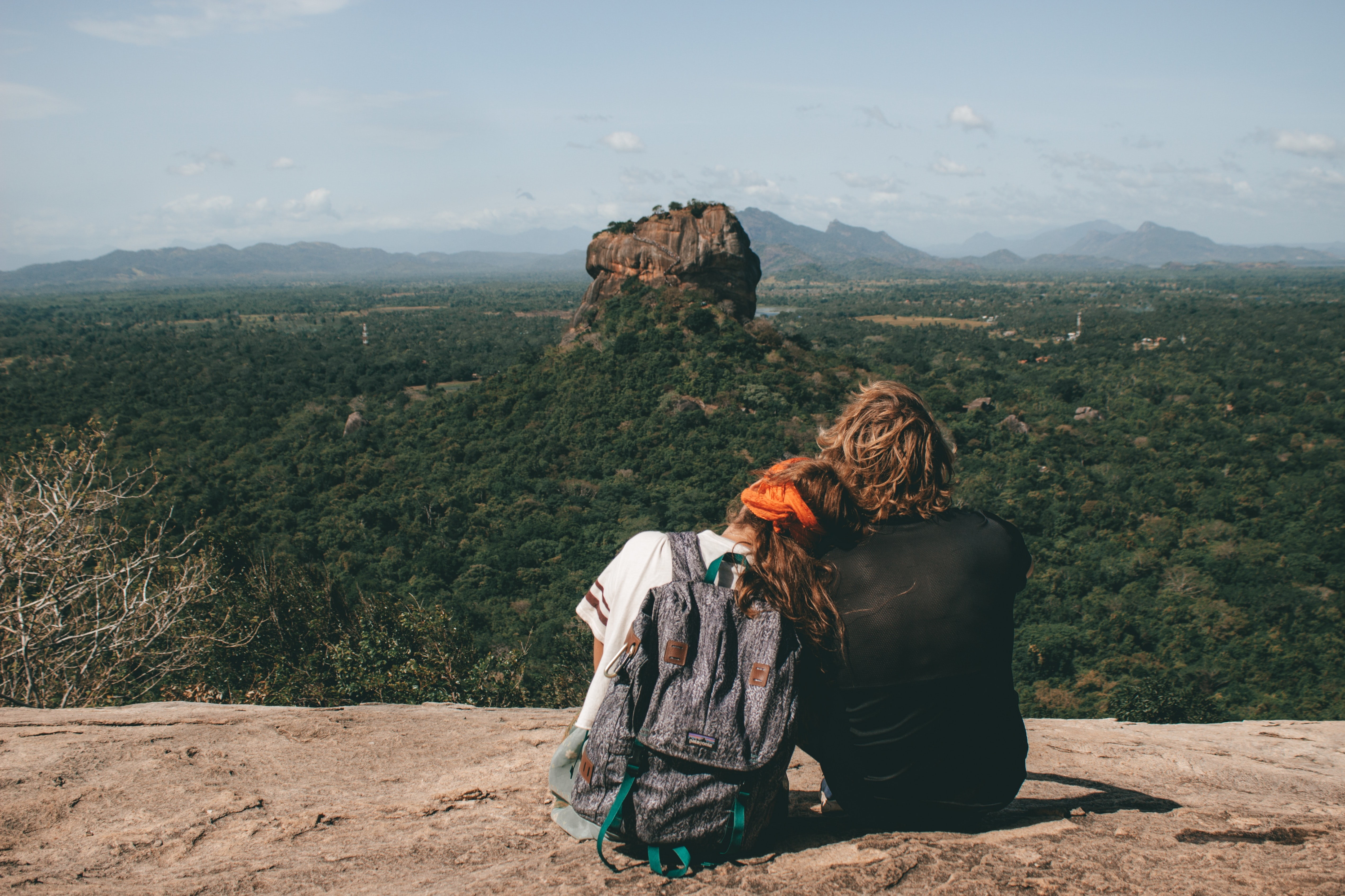man and woman sitting beside cliff