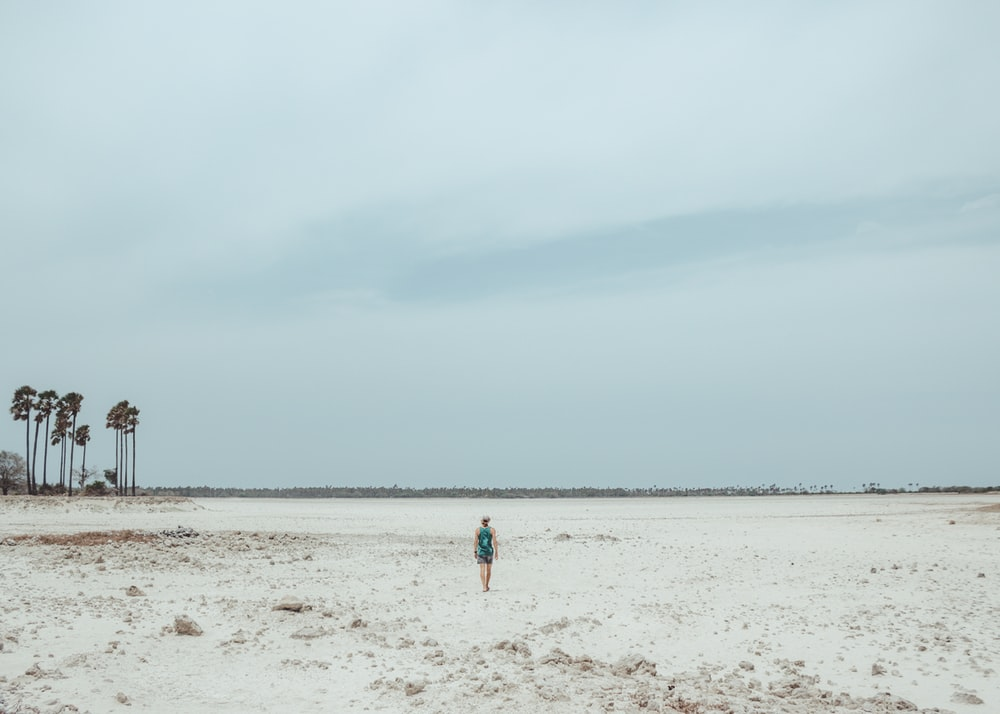 person walking on white sand field
