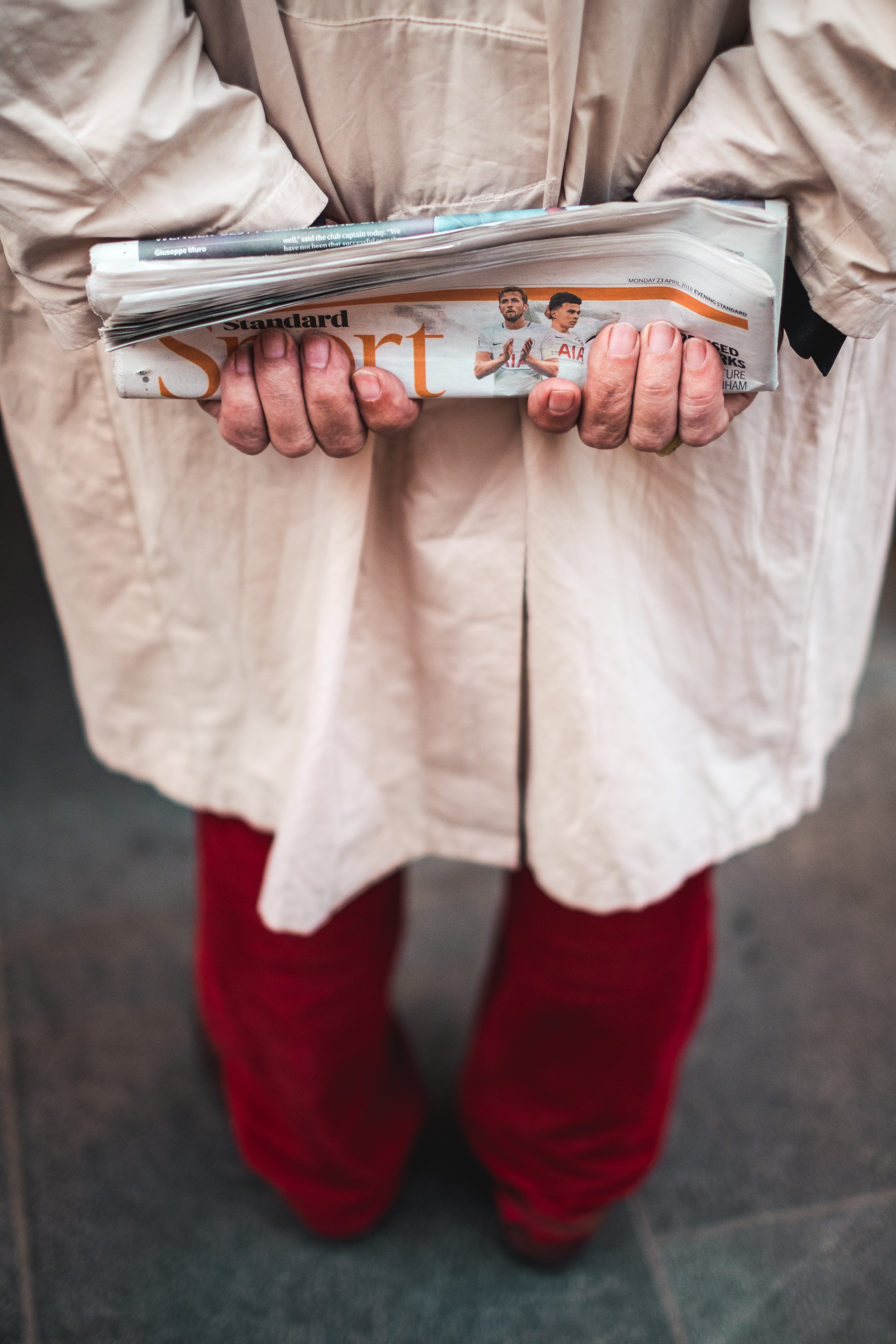 person carrying folded newspaper at back