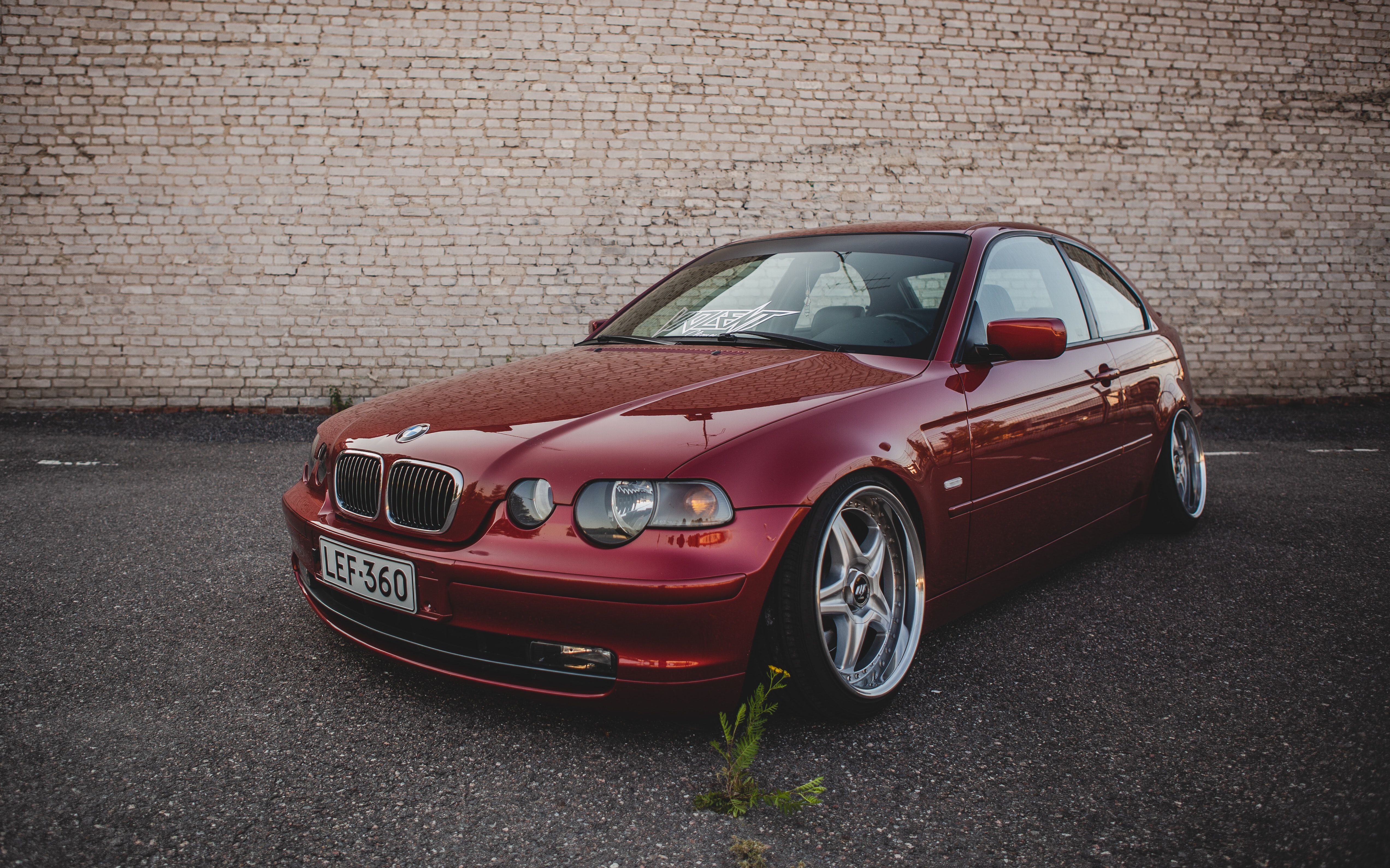 red BMW coupe parked beside brick wall