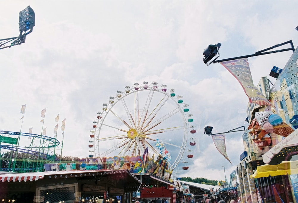 crowd of people in park with ferris wheel