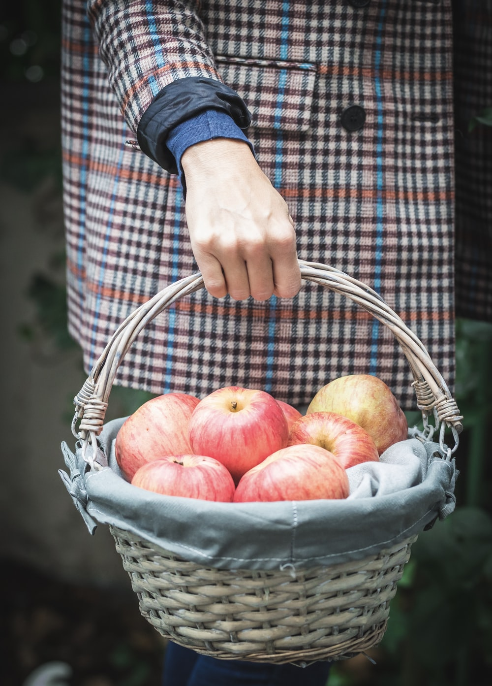 woman holding basket of apple fruits