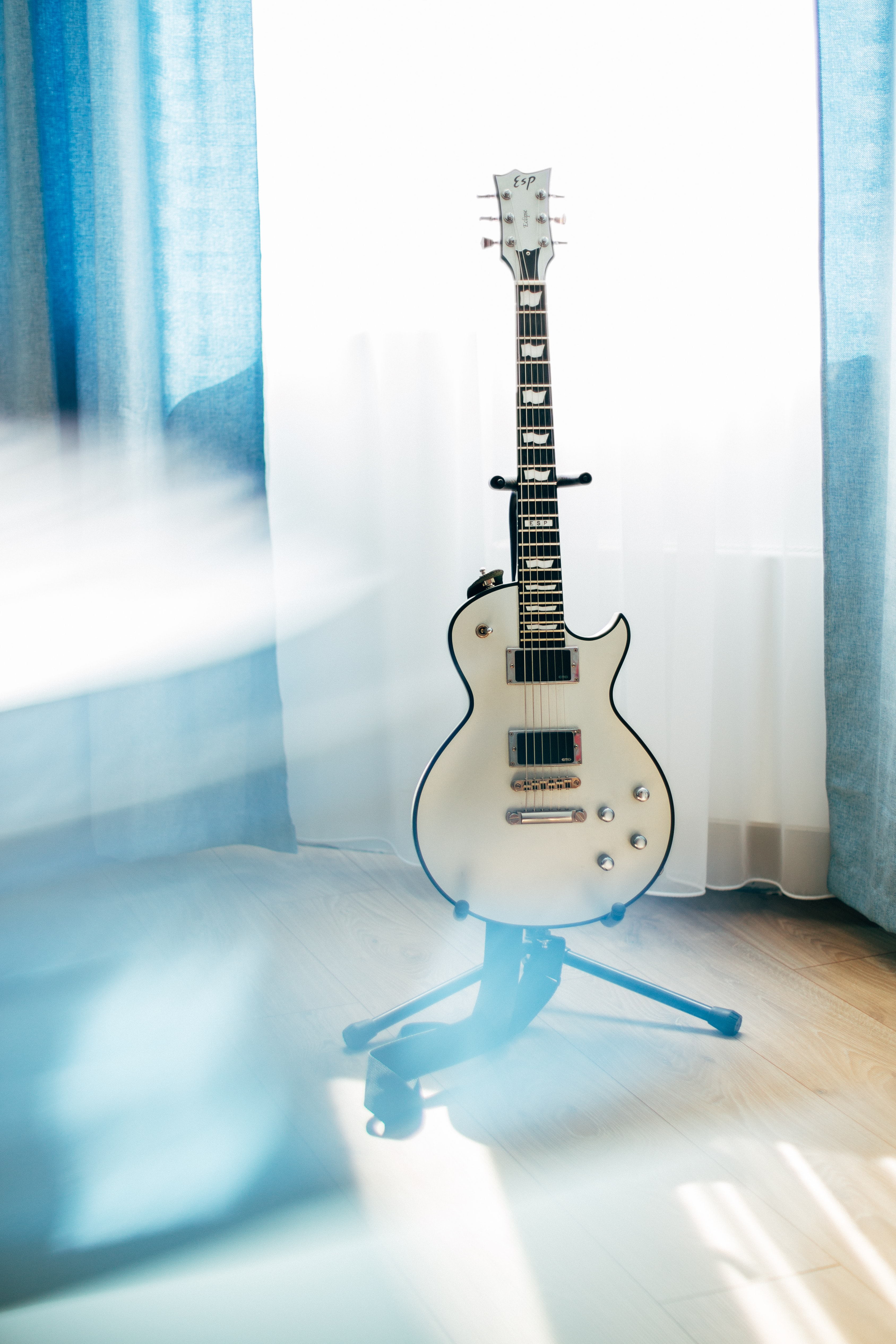 white Les Paul guitar with stand