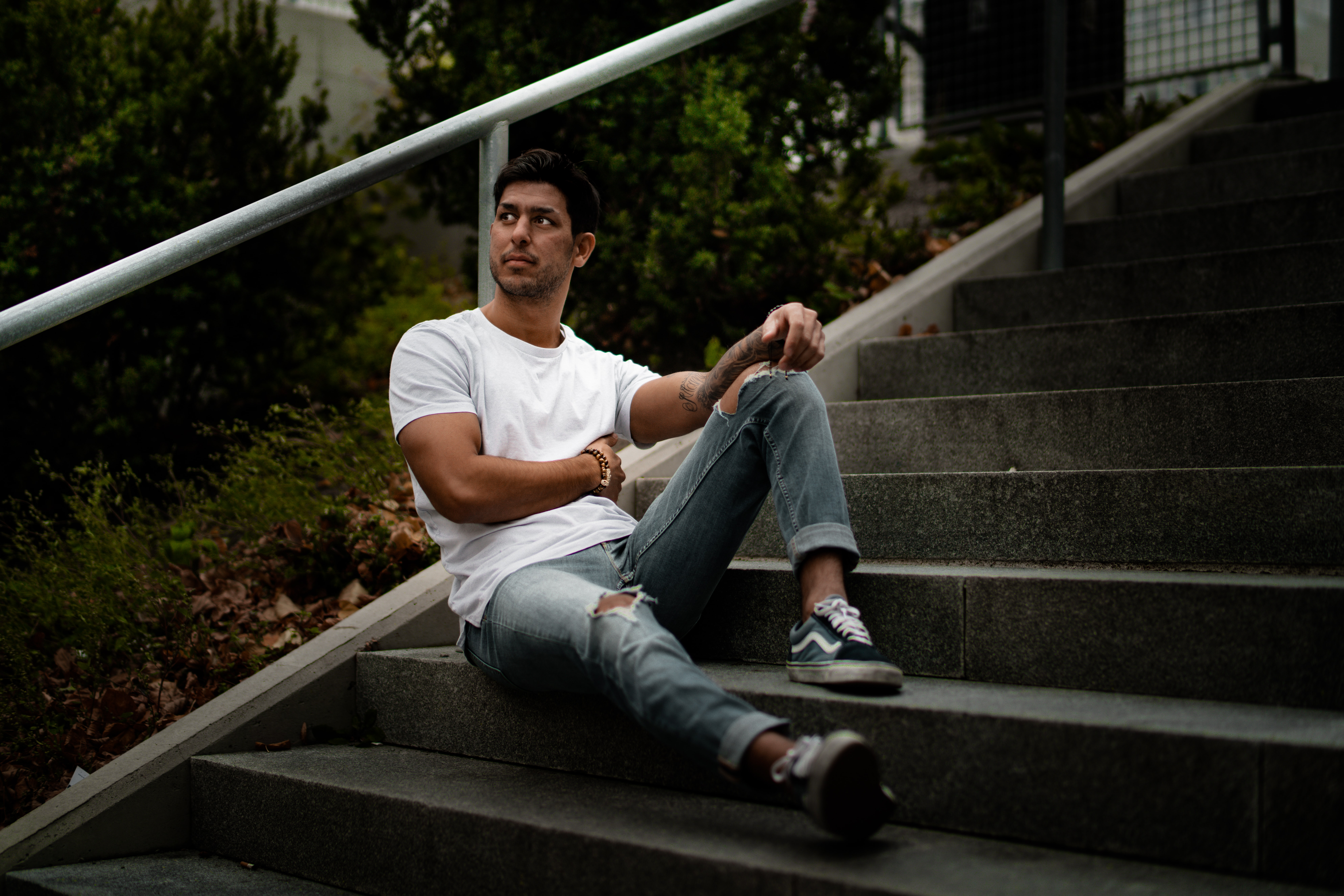 man sitting on stairs leaning against rail