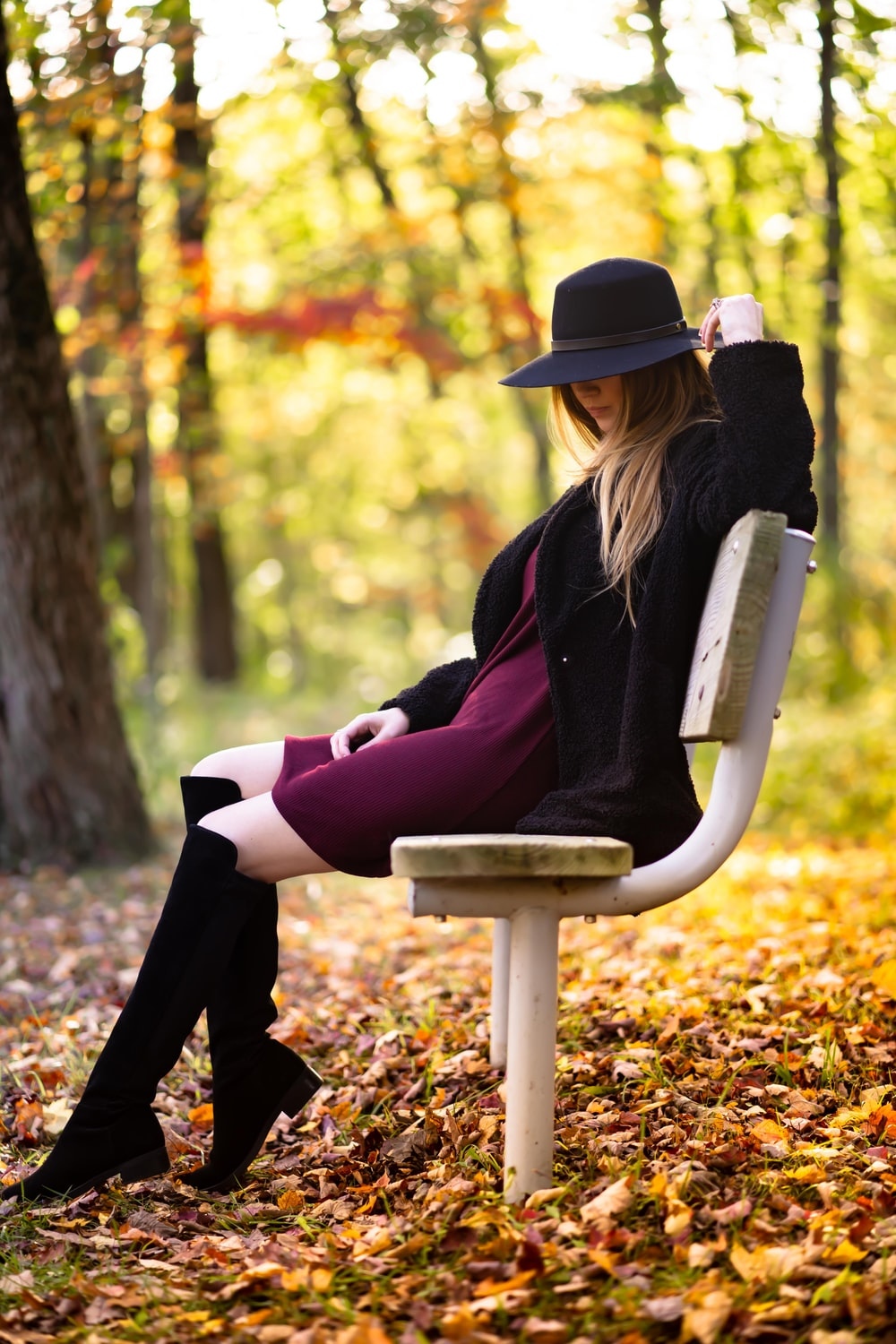 woman wearing black hat sitting on the bench