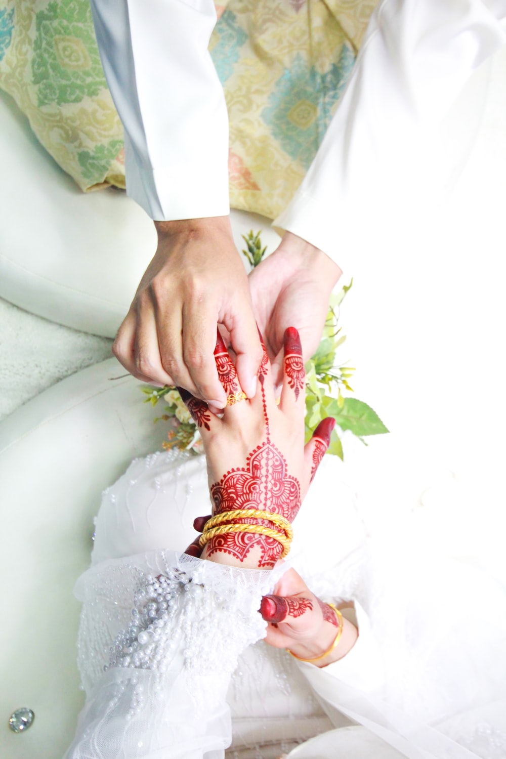 person holding hands with red Mendhi tattoo