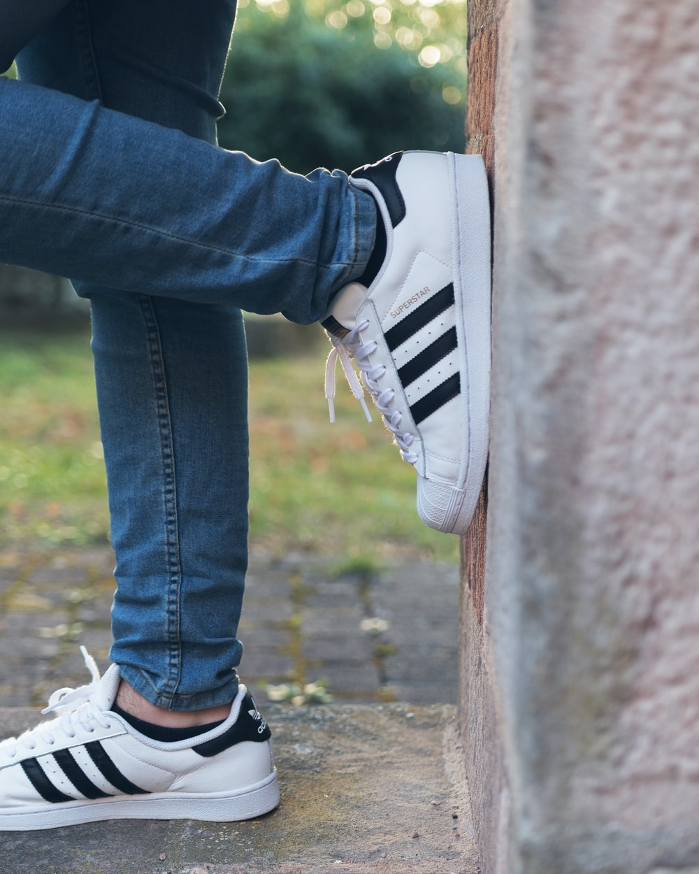person wearing white adidas Superstar while leaning on wall